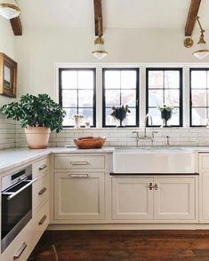 Gorgeous White Kitchen. I am obsessed with the farmhouse sink. Such a beautiful farmhouse kitchen. I love the wood beams too!