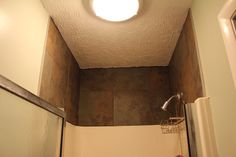 I used the same tile above the shower that I used on the floor and edged it with silver metal.
