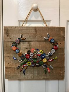 This wall art is made with reclaimed pallet wood and a mixture of bottle caps. The caps are secured with panel nails. The pictures are an example of the finished product. Caps used and the color of the pallet wood vary with each piece. The buyer is welcome to request a picture of the actual piece they will receive prior to shipping. This is a great item for pool houses, beach houses, bars, and perhaps a man-cave. The piece measures 14 tall by 16 wide.