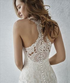 Sensual mermaid wedding dress that plays with the tulle and lace illusions. A very feminine, form-fitting design that streamlines the silhouette. The lacy V-neck and racer back create a very sexy effect. Available at The Princess Bridal in Spring, TX.