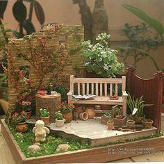 Miniature garden scene. Brick fence. Wood bench. Clay pots. Trees. Diorama scene.