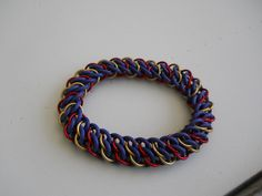 122.  Purple EPDM rubber with gold and red anodized aluminum. Double half Persian pattern bracelet. $20
