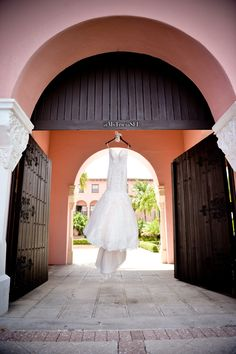Photo by Michelle Lawson Photography. My pale pink/blush desinger wedding dress by Maggie Sottero blowing in the wind at the Boca Resort with a custom made hanger. We couldn't fit my whole last name, so Mrs. W did just fine!  #wedding #weddingideas #gettingdressed #weddingdress #behindthescenes #pinkweddingdress #blushweddingdress #mstriciasfl #weddingphotograhy #weddinghanger #bocaresort #laceweddingdress