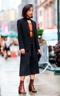 Street style look com blusa amarela, calça culotte preta, blazer e bota animal print.