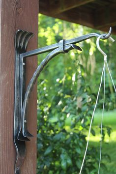 Hang your plants, flower pots, lanterns, feeders and other garden/yard decor with the help of this modern style decorative plant bracket. The bracket is made of solid iron and has a natural wax coated finish. It does not include hardware for installation. Ready to ship. Dimensions: 17.25x13x2.25 inches. Have questions about custom orders, turnaround time or shipping? Contact us online or call 423-441-8230. Thank you for your interest in my work and supporting the arts. -Ryan Schmidt, Mitty's…