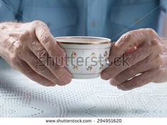 An elderly man drinks tea at home. Senior man holding cup of tea in their hands at table close-up - stock photo