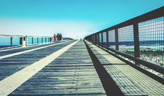 Long fishing pier in Navarre Beach, Florida day, sunlight, transportation, real people, clear sky, built structure, sky, bridge - man made structure, lifestyles, architecture, connection, outdoors, the way forward, men, one person, people