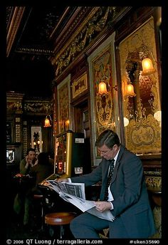 Man reading newspaper in front of etched mirrors, pub Princess Louise. London