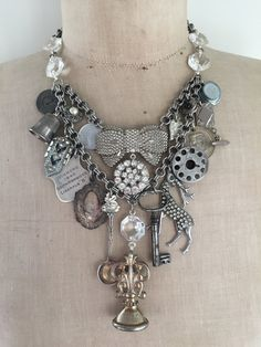 This beautiful steampunk charm necklace is jam packed with a mass of genuine vintage and antique charms, momentos and curios. The pieces are:  - an antique letter seal (I think the letter is a curcuve H), - skeleton key, - tiny salt spoon (says Canada), - deer brooch, - antique ornate shield (perfect for engraving if you so desire), - vintage sewing machine bobbin, - trophy shield from 1940 (its hall marked and I believe sterling silver), - a medallion from 2936 commemorating the 42nd…