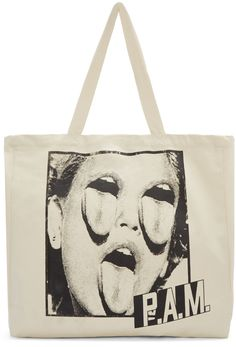 Unstructured canvas tote bag in 'ecru' ivory. Twin carry handles at top. Graphics screen printed in black at face and back face. Press-stud fastening at sides and bag throat. Zippered pocket at interior. Silver-tone hardware. Tonal stitching. Approx. 20