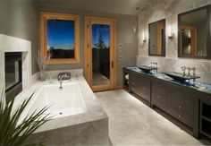 This lovely modern bathroom features a stunning espresso double vanity.  Black pedestal sinks arise from the glass covered collection of river stones, and bring to mind feng shui sensibilities of design.  Simple metal spigots hover over each basin, and coordinate with unobtrusive metal drawer pulls.