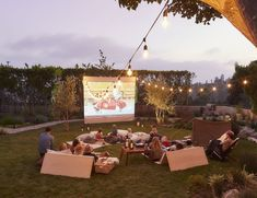 Outdoor movie night with canvas drop cloth clamped to a plumbing pipe frame and hinged plywood back rest loungers for sitting on the ground with blankets. So cool!