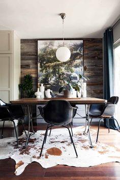 idée déco salle à manger - tableau paysage forestier accroché au panneau mural en bois, chaises noires et tapis en peau de vache