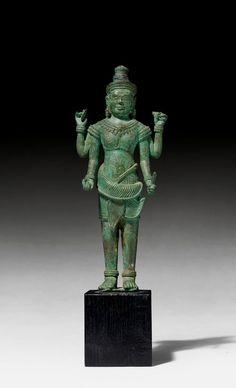 STEHENDER VISHNU. Khmer, Stil des Bayon, 13. Jh. H 22 cm. Bronze mit grüner Patina. Die vierarmige Gottheit hält seine Attribute, das Rad, die Muschel, den Knüppel und die Knospe. Der kurze fein plissierte Sampot ist breitzipflig in der Mitte verschlungen. Ein prächtiger Brustschmuck sowie schwere Ohrgehänge und eine schmale Krone vervollständigen die Erscheinung.