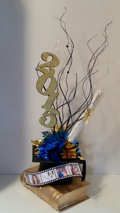 Graduation centerpiece Choose your colors  Centerpiece has, Book, picture film, black cap with black tassel, metallic colored fillers, diploma personalized, year in glitter, and wooden swirls. About 2.5 ft tall