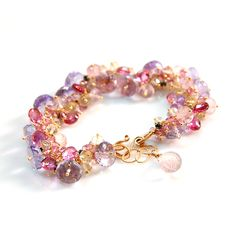 Hundreds of pastel hued gemstones including pink sapphires, tourmaline, rose quartz, lavender amethyst, yellow sapphires, topaz and flecks of pyrite are hand-linked together, one by one on handcrafted headpins, to form this incredibly feminine and delicate bracelet. The piece is finished with our signature hook clasp and intricate hand-wrapped loops with a half inch extender chain to allow the wearer to adjust the length. Available in 18K gold, 14K gold, .930 Argentium silver and 14K…