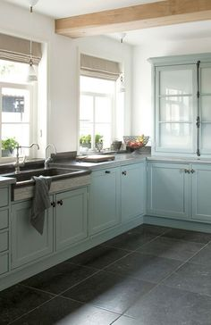 Aqua blue kitchen with bluestone floors. Love the cremone bolt on the far cabinet.