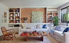 """A sala da apresentadora Patricya Travassos é aconchegante. Segundo a designer de interiores Paola Ribeiro, a ideia foi valorizar a madeira e os tijolos de demolição. """"Esses elementos remetem à sensação de casa, mesmo sendo de apartamento"""", explica"""