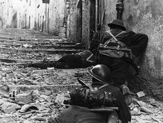 Over the body of a dead comrade, Canadian infantrymen advance cautiously up a narrow lane in Campochiaro, Italy, on November 11, 1943. The Germans left the town as the Canadians advanced, leaving only nests of snipers to delay the progress.