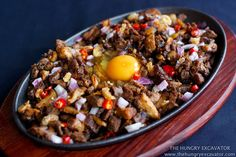 Sizzling Pork Sisig. Pork parts (often: head, liver, cheeks) mixed with onions, chiles, citrus, and egg.