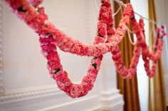 Equal parts pretty and glamorous, skinny garlands made from pink flowers are perfect for a girlie bridal shower. Photo by Jasmine Star via Source