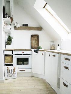 Aranżacja małej kuchni bezpośrednio pod skosami, która wiele zyskuje na wszechobecnym białym kolorze. Jasna przestrzeń...