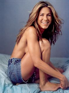 #jenniferaniston #topless Jennifer Aniston topless in blue jean short sitting on bed smiling with white painted toe nails while holding her feet