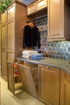 Wow! At first I though I was looking at a kitchen. Nope, this is a laundry room  with lots of counter space for folding, a bar for hanging up clothes, and pull out / slide out storage shelves and bins for detergents and such. - Style: Columbia; Species: Maple; Color: Tuscan; Finish: Black Glaze