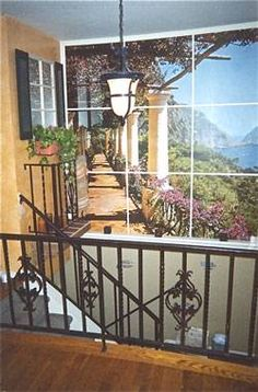 foyer with wrought iron staircase railing which is painted black with faux rust. Also a Tuscan Mural framed to simulate a window, and a faux balcony completes the Medeterranian look