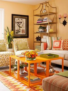 A living space with small cubed tables instead of a larger coffee table. I love all the pattern in this photo. The tall shelf works and doesn't overwhelm the space because it is open.
