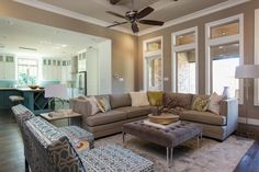 Neutral walls, a neutral area rug and a large neutral sectional set the stage for this contemporary living room. Blue geometric chairs add a pop of stylish color to the earth tones, and throw pillows on the sectional add touches of yellow, green and blue.