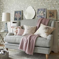 Grey sofa in front of floral wallpaper