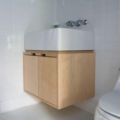 Maple floating bathroom vanity with sink top against white subway tile. Simple plywood cabinet by Kerf Design. kerfdesign.com