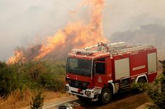 Flames rise next to a fire truck as a wildfire rages at the village of Neapoli on July 17, 2015.