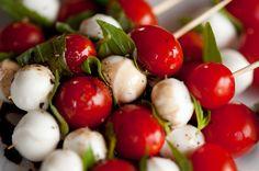 Caprese skewers--mozzarella balls, cherry tomatoes, basil, and vinaigrette