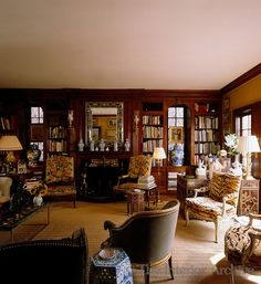 my fantasy NYC sitting room with floral and leopard print chairs, blue and white porcelain, a desk, art, books and fireplace