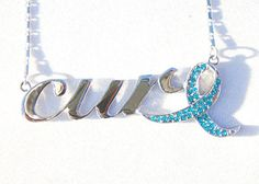 Cure Necklace with Teal Ribbon by GSJ brings awareness to Ovarian Cancer, Cervical Cancer & Uterine Cancer.