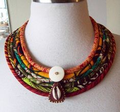 I combined six African fabrics with a horn disc and vintage red leather cowrie shell adornment.  Necklace is light weight and all fabric cords