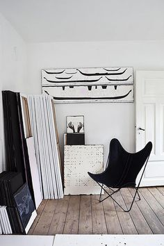 a black butterfly chair and amazing black and white art