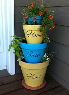 Stacked Flower Pots. Spray painted terra cotta pots to give them new life. Added vinyl lettering.
