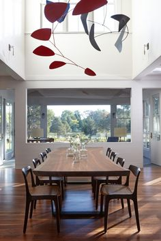 Dining room with large wooden table and Calder hanging mobile fullfillin the double ceiling. Project by Breese Architects and Interiors Studio Martha's Vineyard