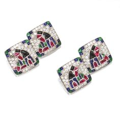 PAIR OF COLORED STONE AND DIAMOND CUFFLINKS, CIRCA 1920, FRENCH Each composed of 2 square links decorated with stylized pharaoh motifs, set with calibré-cut rubies, emeralds, sapphires and onyxes, accented by single-cut diamonds, mounted in platinum and 18 karat gold, French assay marks.