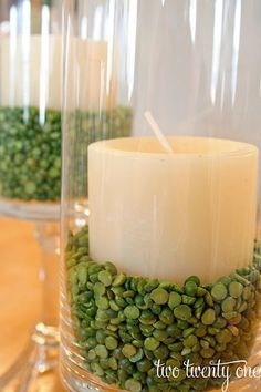 Split Peas (Yellow & Green) & Candles as floral arrangements. SAM-if the stone idea doesn't work for your centre pieces you could use this perhaps :) Hurricane Centerpiece, Hurricane Candle, Candle Vases, Vase Fillers, Decoration Table, Spring Decorations, Vases Decor, Home And Deco, Green Wedding