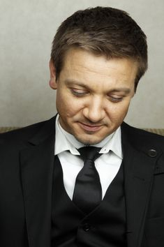 Jeremy Looking Down and Wearing a White Button-Up Shirt and Black Suit