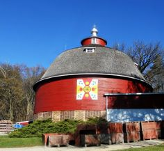 A round barn! This barn in Green County, Wisconsin -- it's wearing a barn quilt! This barn is located at the local apple orchard. The center of the quilt is taken from a Hex Sign that has hung on the barn for years and has become something of a logo for the business. The custom-designed barn quilt is called Apple a Day!