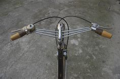 Wow^3!!! Stem integrated custom chrome  handlebars with wood and tortoiseshell grips and a nice temple bell. That's style.