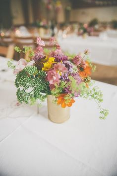 Image by  Millie Benbow Photography - A Phase Eight wedding dress for a vintage inspired village hall wedding with handpicked wild flowers and floral bridesmaid dresses.