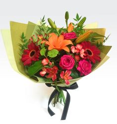 Luscious mixed bouquet of rich ruby red and vibrant orange tones with complimenting lush green foliage.