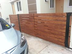 Horizontal wooden fence. Made from Gmelina arborea (white teak) hard wood with American walnut stain.