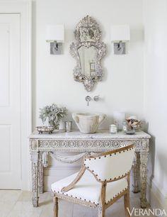 Louis XVI console, Tara Shaw Antiques; sink fittings, Grohe; sconces, Restoration Hardware; 18th-century Swedish armchair in a Libeco linen; floor tiles, Walker Zanger.   - Veranda.com